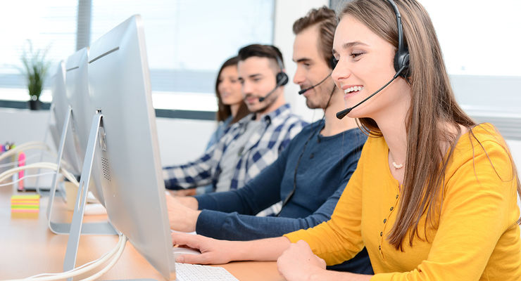 portrait of beautiful and cheerful young woman telephone operator with headset working on desktop computer in row in a customer service call support helpline business center with teamworker in background